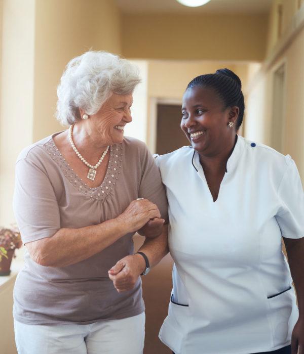 Senior lady and nurse walking down a hallway together