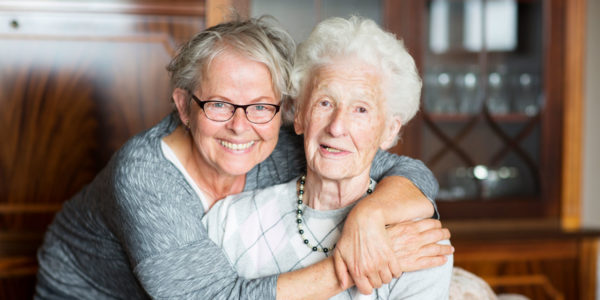 Woman hugging senior lady