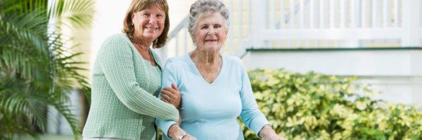 A woman helping elderly lady walk with a cane