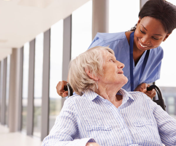 Nurse pushing a woman in wheelchair.