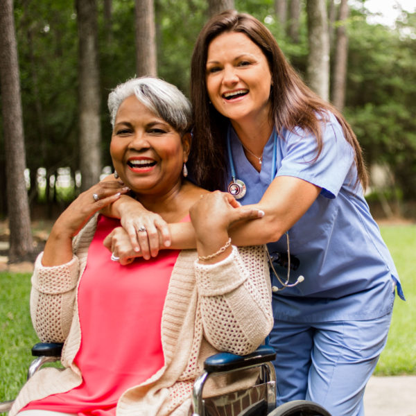 Nurse hugging lady in wheelchair